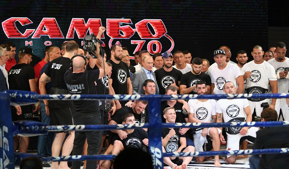 Władimir Putin fotografuje się z uczestnikami międzynarodowego turnieju sambo