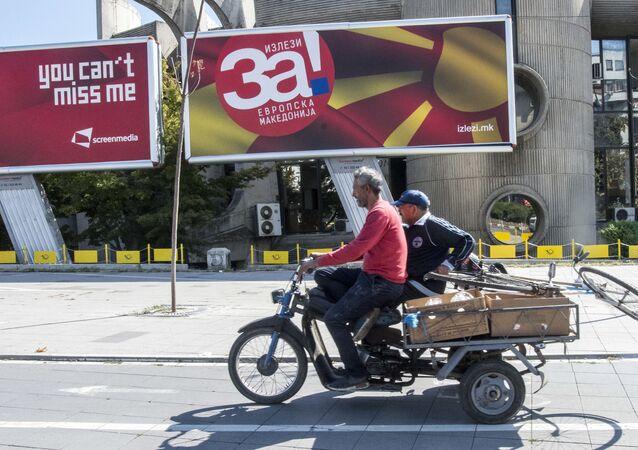 Mężczyzna przejeżdża motorowerem obok billboardu z reklamą referendum