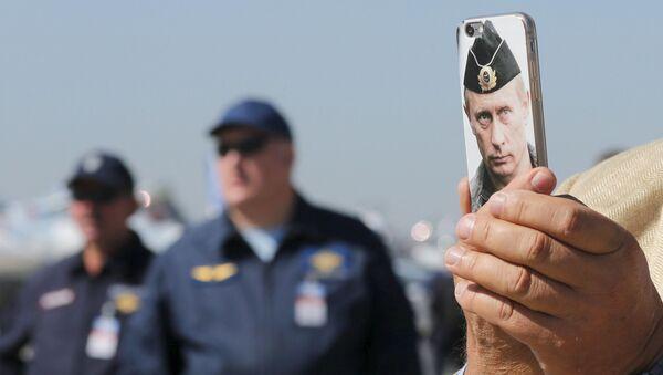 Gość Międzynarodowego salonu lotniczego i kosmicznego MAKS - 2015 robi zdjęcia komórką z obrazkiem prezydenta Rosji Władimira Putina - Sputnik Polska