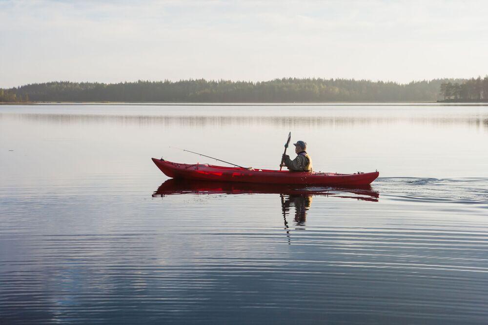 Rybak pływa na kajaku wzdłuż jeziora w Karelii