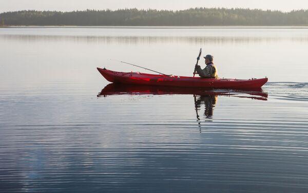 Rybak pływa na kajaku wzdłuż jeziora w Karelii - Sputnik Polska