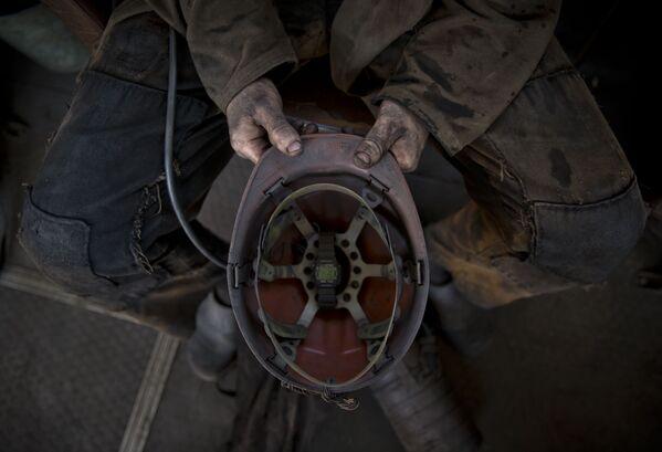 Górnik trzyma kask w jednej z kopalń Doniecka - Sputnik Polska