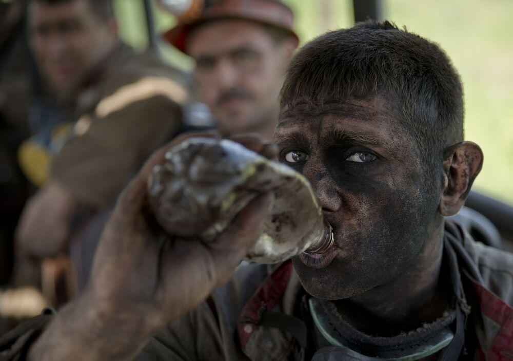 Doniecki górnik pije wodę po wyjściu z kopalni