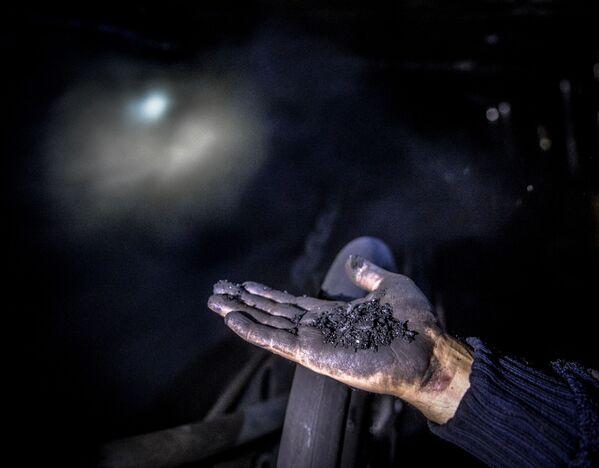 Górnik pokazuje węgiel w kopalni Głubokaja w Szachtarśku w obwodzie donieckim - Sputnik Polska