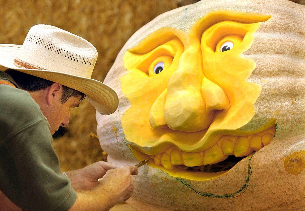 Artysta Mike Vallado podczas pracy nad wizerunkiem twarzy z dyni
