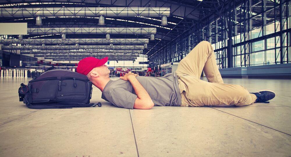 Mężczyzna leży na podłodze w oczekiwaniu na lot