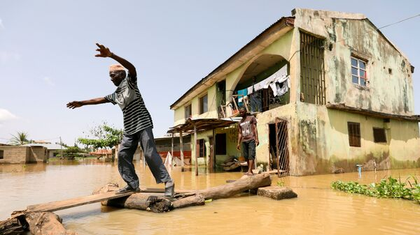 Жители нигерийского штата Коги на затопленной после наводнения улице - Sputnik Polska