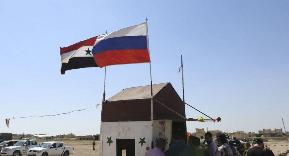 Flaga syryjska i rosyjska po wschodniej stronie korytarza humanitarnego Abu Duhur w syryjskiej prowincji Idlib