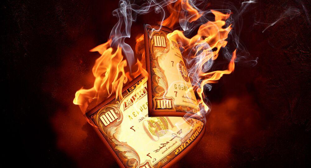 Palący się studolarowy banknot