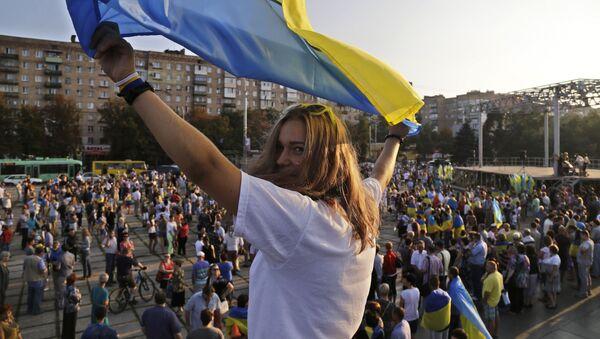 Dziewczyna z ukraińską flagą na antywojennym wiecu w Mariupolu - Sputnik Polska