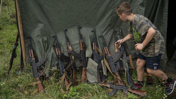 """Chłopiec obok karabinów AK-47 w letnim zmilitaryzowanym obozie dziecięcym """"Temper of will"""" zorganizowanej pod Tarnopolem na Ukrainie - Sputnik Polska"""