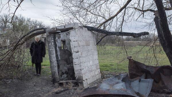 Kobieta stoi przed swoim zniszczonym domem w wiosce Sachanka pod Donieckiem - Sputnik Polska