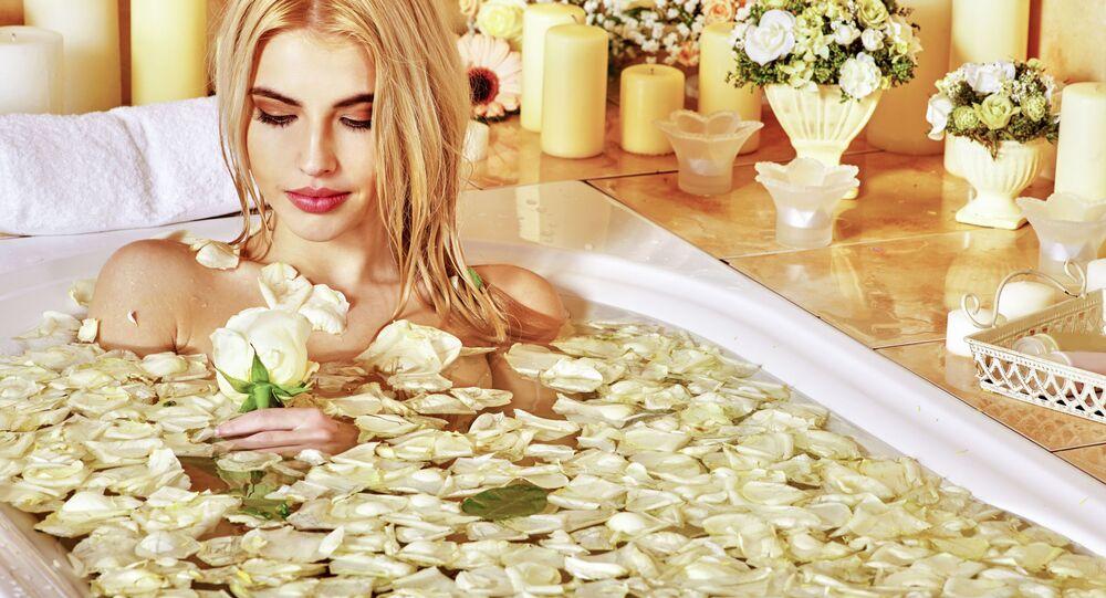 Kobieta kąpiąca się w wannie z płatkami białych róż