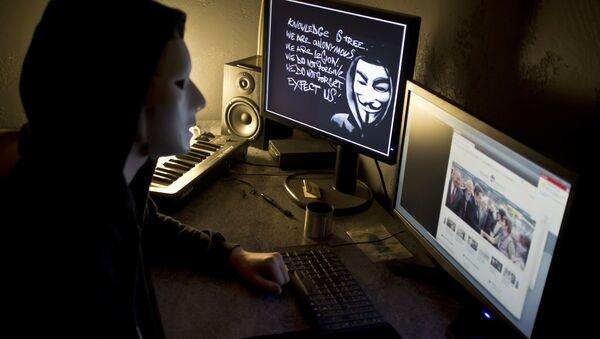 Haker z Anonymous przed ekranem komputera - Sputnik Polska