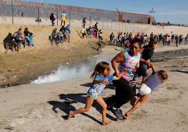 Migranci z Hondurasu uciekają przed gazem łzawiącym użytym przez straż graniczną USA