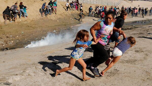 Migranci z Hondurasu uciekają przed gazem łzawiącym użytym przez straż graniczną USA - Sputnik Polska