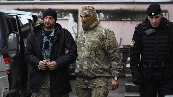 """Jeden z zatrzymanych marynarzy z okrętów Marynarki Wojennej Ukrainy """"Berdiańsk"""", """"Nikopol"""" i """"Jany Kapu"""" (po lewej) pod Sądem Rejonowym Symferopola, gdzie rozpatrywany jest wybór środka zapobiegawczego - Sputnik Polska"""