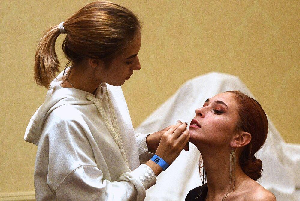 Wizażystka wykonuje makijaż modelce podczas finału konkursu piękności Top Model Rosji 2018 i Top Model PLUS 2018