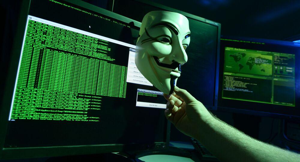 Maska Guya Fawkesa przed ekranami komputerów.