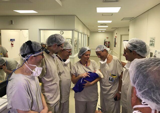 Lekarze z dzieckiem, które urodziła kobieta po przeszczepie macicy od zmarłego dawcy