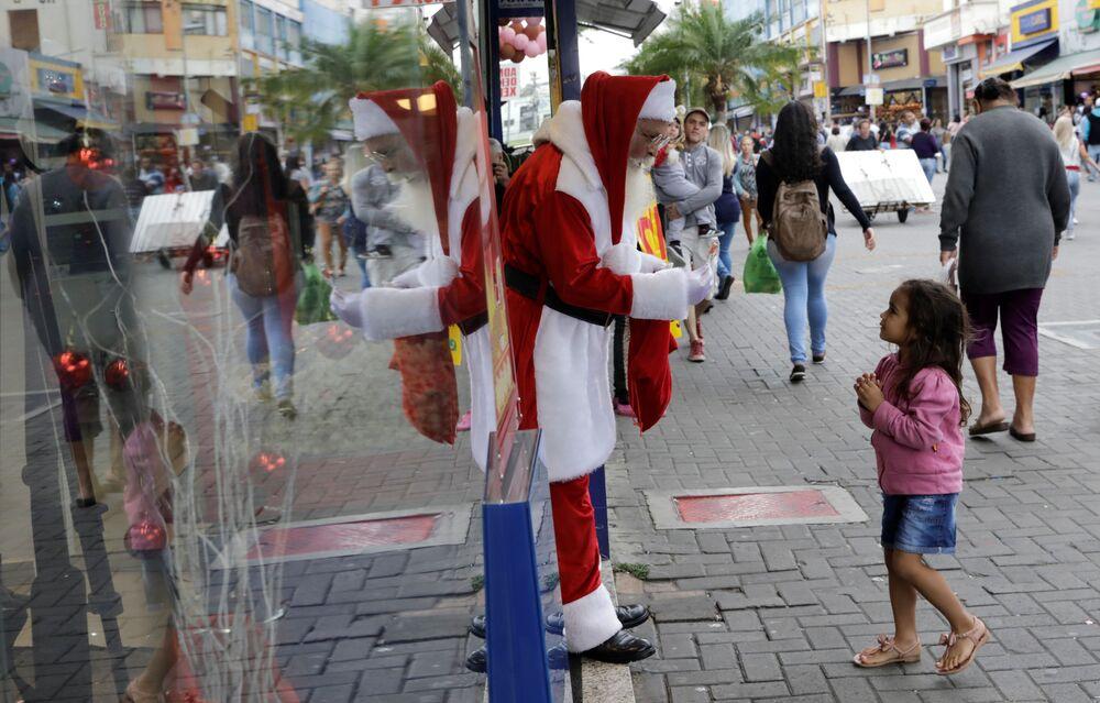 Święty Mikołaj częstuje dziewczynkę cukierkami, Brazylia