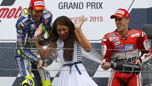 Motocykliści Valentino Rossi i Andrea Dovizioso świętują zwycięstwo i oblewają dziewczynę szampanem podczas ceremonii nadradzania - Sputnik Polska