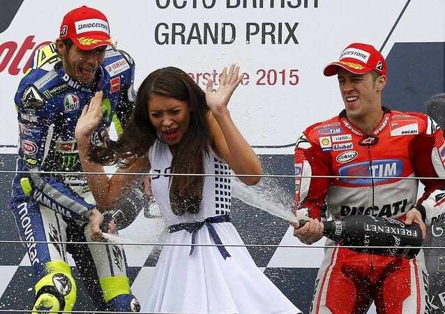 Motocykliści Valentino Rossi i Andrea Dovizioso świętują zwycięstwo i oblewają dziewczynę szampanem podczas ceremonii nadradzania