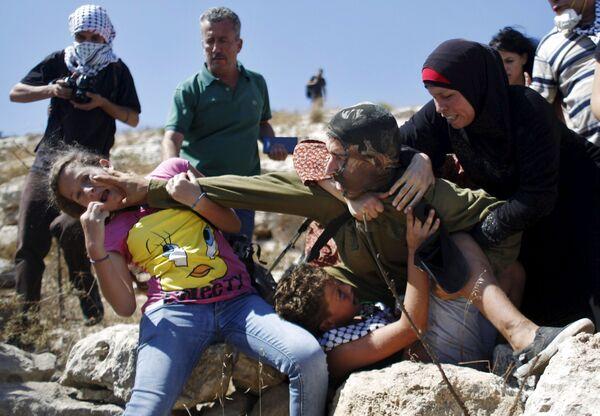 Palestyńczycy biją się z izraelskim żołnierzem podczas akcji protestacyjnej przeciwko osiedlom żydowskim pod Ramallah - Sputnik Polska