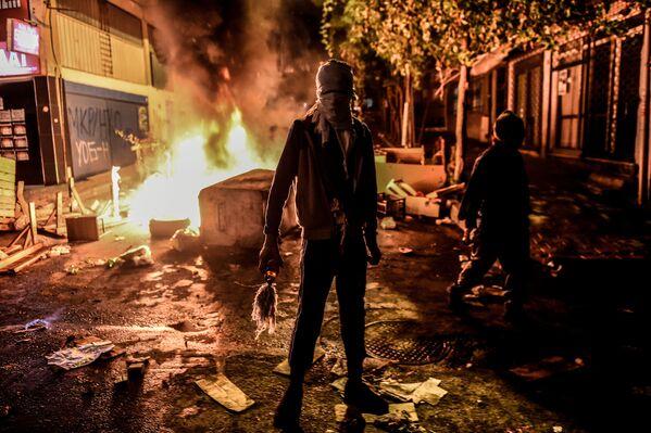 Protestant trzyma butelkę zapalającą podczas starcia z policją w Stambulu - Sputnik Polska