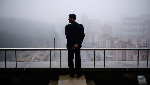 Mężczyzna na balkonie domu w Pjongjangu - Sputnik Polska