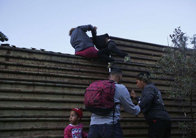 Migranci przechodzą przez mur na granicy USA i Meksyku