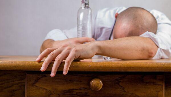 Pijany mężczyzna z butelką przy stole - Sputnik Polska