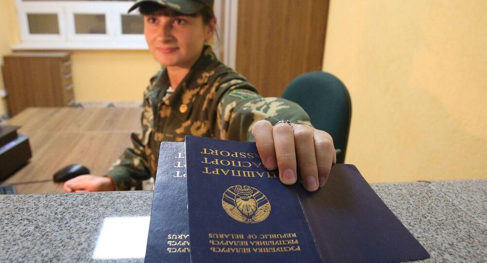 """Strażnik graniczny sprawdza paszporty na przejściu granicznym między Białorusią a Polską """"Pererow""""."""