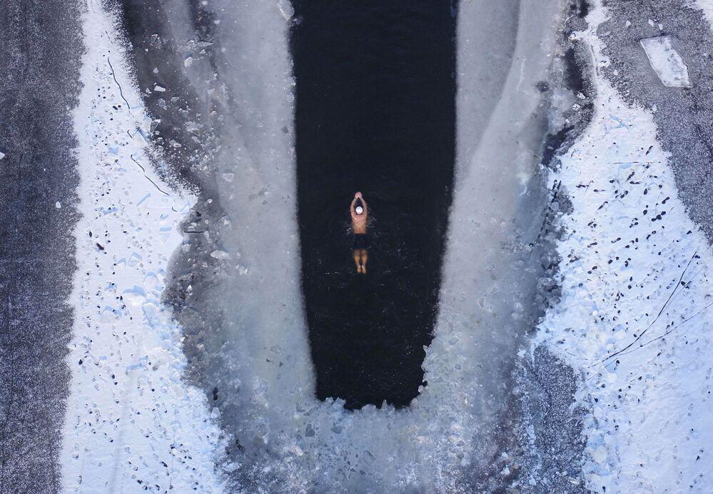 Mężczyzna pływa w częściowo zamarzniętym jeziorze w Shenyang