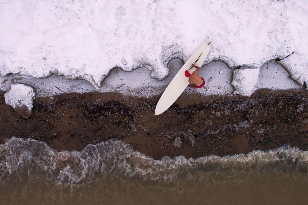 Sportowiec Aleksander Orlov zamyka sezon windsurfingowy na brzegu zbiornika hydroelektrycznego w Nowosybirsku w temperaturze około -5 ° C
