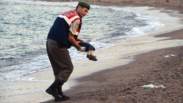 Policjant niesie ciało syryjskiego chłopca Aylana Kurdi - Sputnik Polska