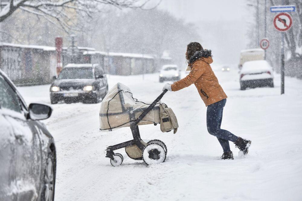 Kobieta z wózkiem na zaśnieżonej ulicy Bratysławy, Słowacja