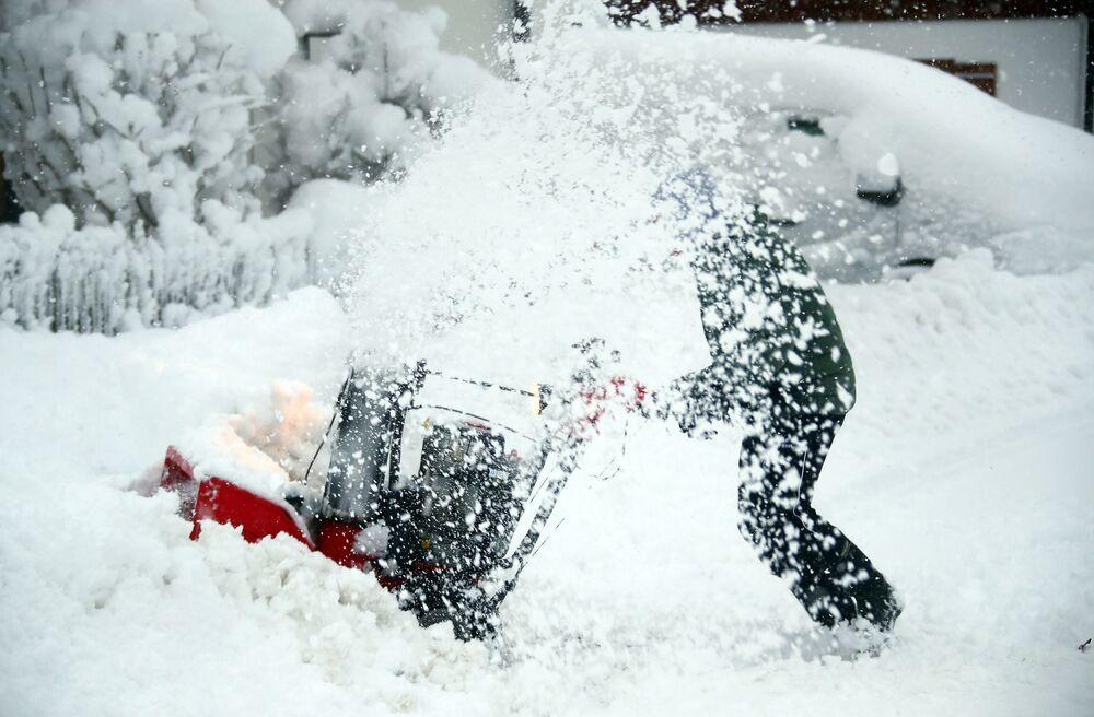 Mężczyzna oczyszcza drogę ze śniegu w Niemczech