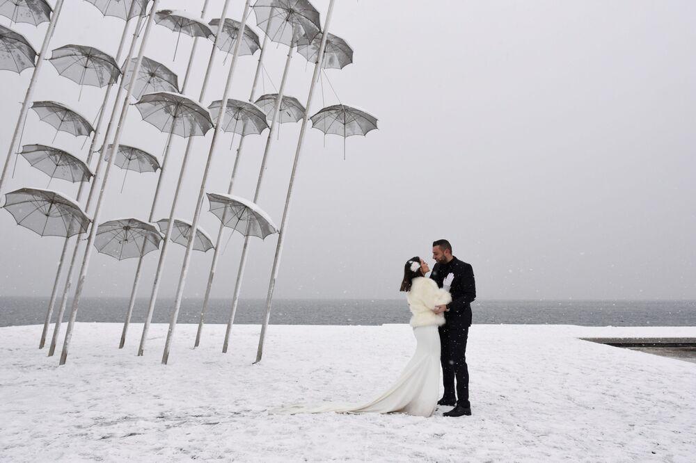 Nowożeńcy na brzegu morza podczas opadów śniegu w Grecji