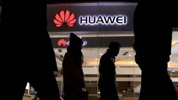 Przechodnie mijają sklep Huawei w Pekinie - Sputnik Polska