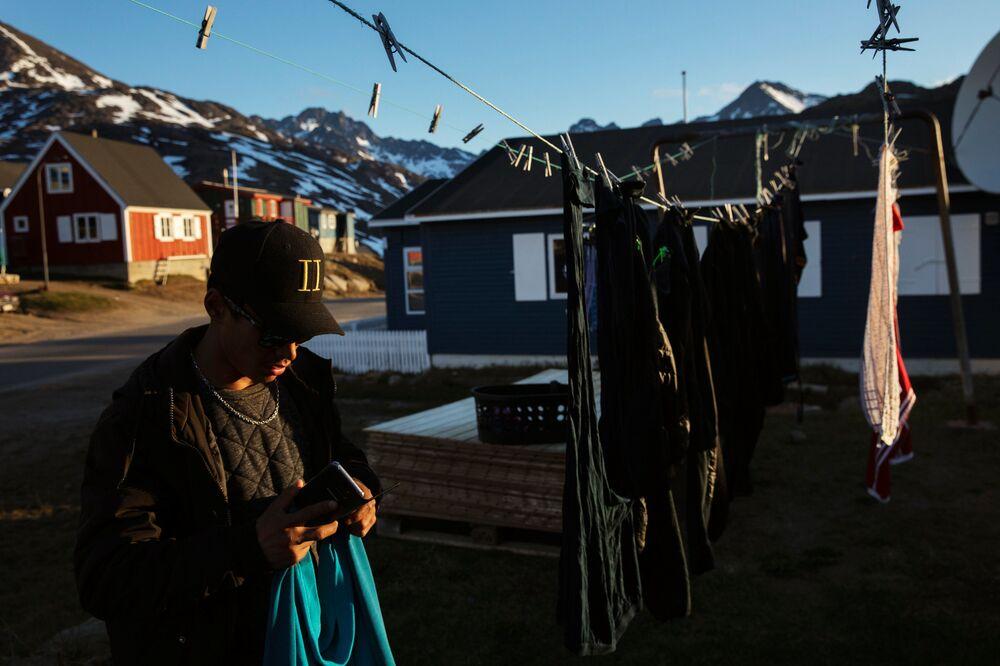 Mężczyzna rozwiesza pranie. Tasiilaq, Grenlandia