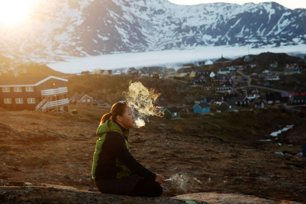 Młoda kobieta pali papierosa. Tasiilaq, Grenlandia