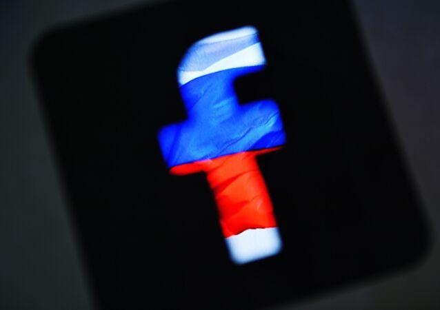 Logotyp sieci społecznościowej Facebook na tle rosyjskiej flagi