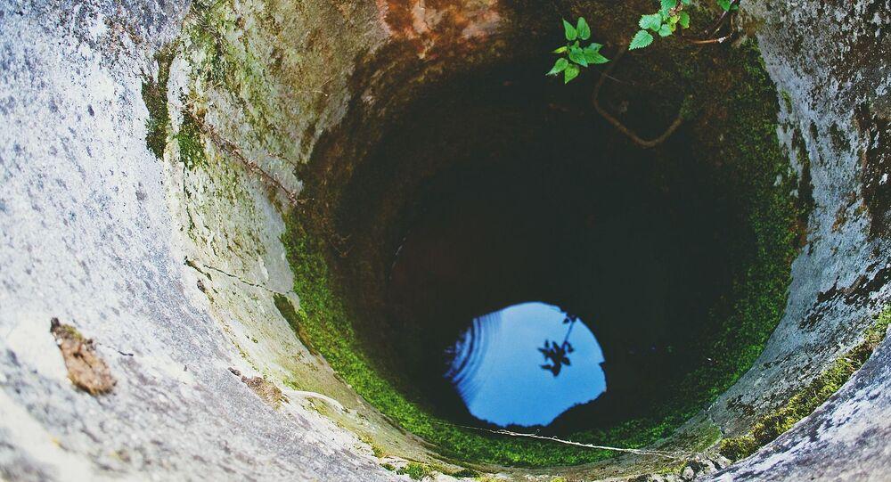 Niebo odbijające się w wodzie na dnie studni
