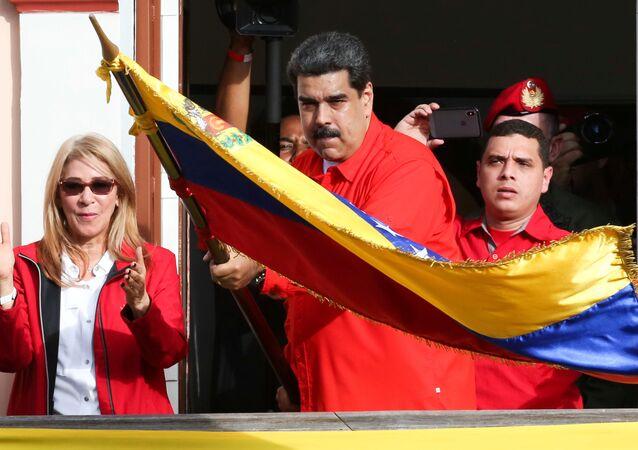 Wenezuelski prezydent Nicolas Maduro z flagą Wenezueli podczas wiecu wspierającego jego rząd