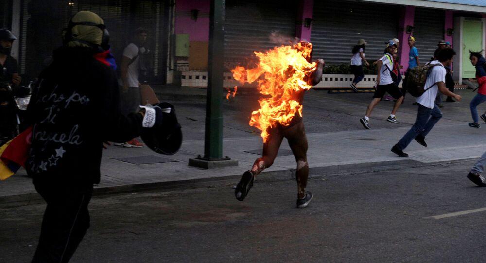 Mężczyzna objęty płomieniami biegnie ulicą w czasie masowych protestów przeciwko polityki Maduro w Wenezueli