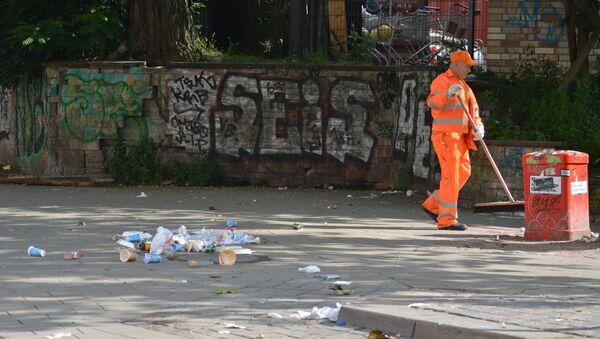 Pracownik służby miejskiej w Hamburgu zamiata śmiecie po akcji protestu - Sputnik Polska