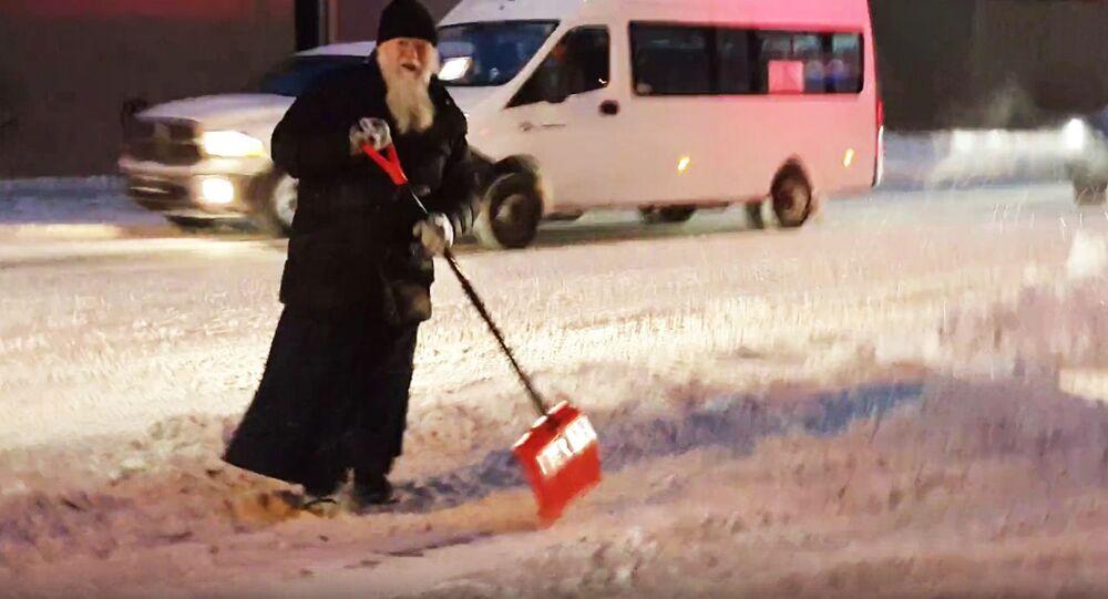 Pop odgarnia z ulicy śnieg
