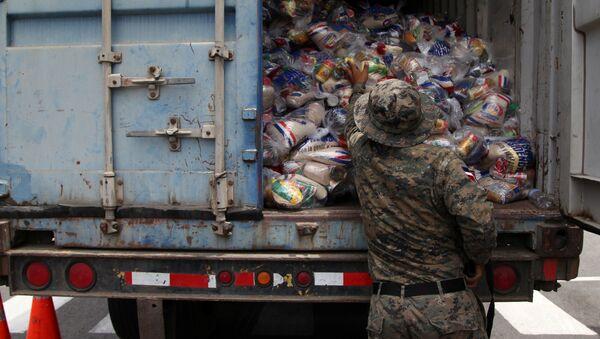 Wojskowy sprawdza paczki żywnościowe w czasie przygotowań do nadejścia huraganu Maria na Dominikanie - Sputnik Polska
