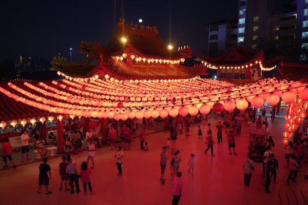 Uczestnicy obchodów Chińskiego Nowego Roku pod oświetleniem świątyni w Malezji - Sputnik Polska